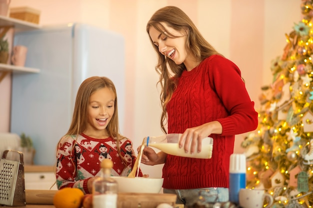 Kid and her mom cooking together in the kitchen