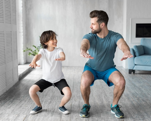 Kid and his father doing sport at home