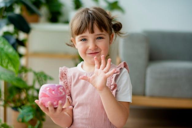 Ребенок держит раскрашенный горшок для цветов своими руками