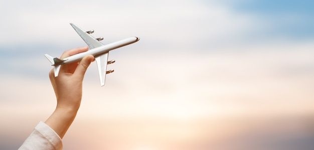 Kid holding airplane in hands and flying over the sunset background