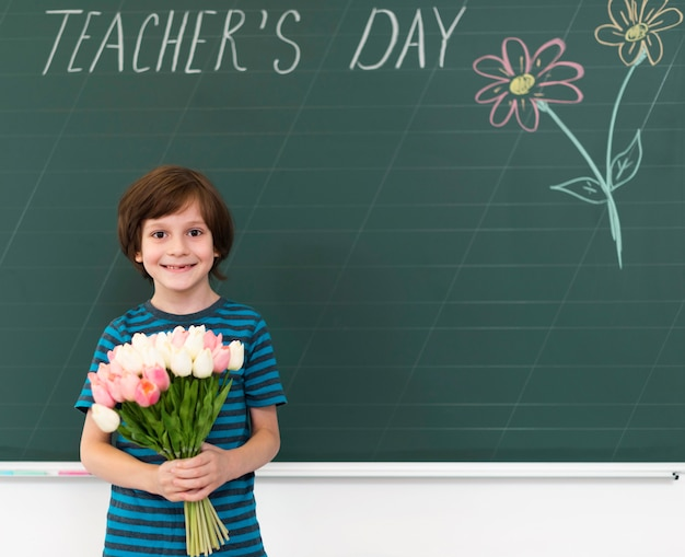 Kid holding a bouquet of flowers next to a blackboard