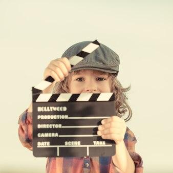 Kid holding clapper board in hands. cinema concept. retro style