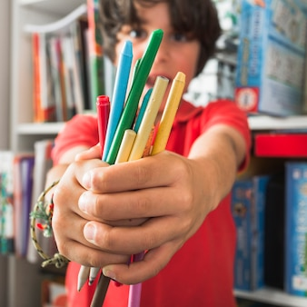 Kid holding drawing pencils