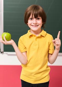 Bambino che tiene una mela verde