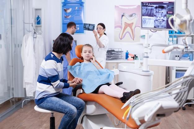 親を見て歯科治療後の痛みのために顔に手をつないでいる子供。歯の間に母親と一緒にいる子供は、椅子に座っている口内検査で診察します。