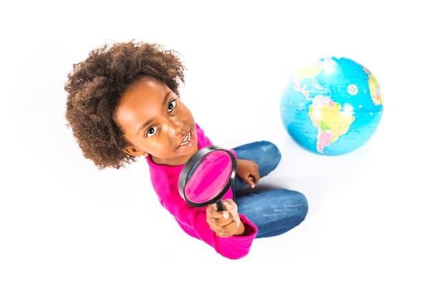 地球儀を持つスタジオで子供を保持するルーペ
