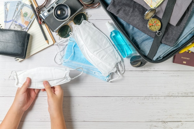 Малыш держит маску и чемодан, старинный фотоаппарат, ноутбук, карту на белом дереве и копией пространства. путешествия и предотвращение covid 19 концепции
