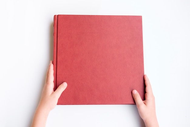 Kid holding red leather covered photobook