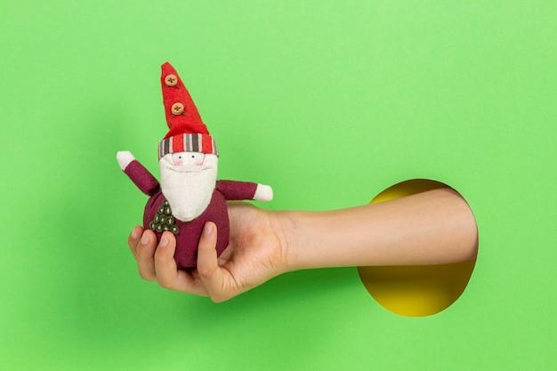 밝은 녹색 배경에 구멍을 통해 손에 빨간 작은 크리스마스 산타 클로스를 들고 아이