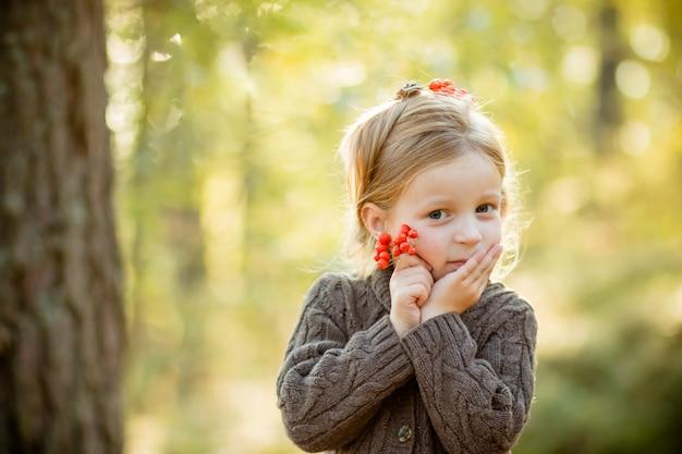 Kid holding rowan berries.