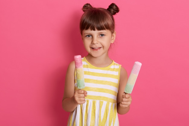 Оягнитесь держать 2 мороженого, счастливую маленькую девочку наслаждаясь водяным льдом, милый ребенок пробуя вкусную еду улицы в лете, представляя изолированный над розовой стеной.
