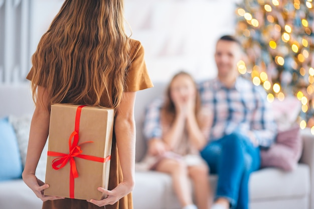 A kid holds a gift box near the christmas tree on of her family