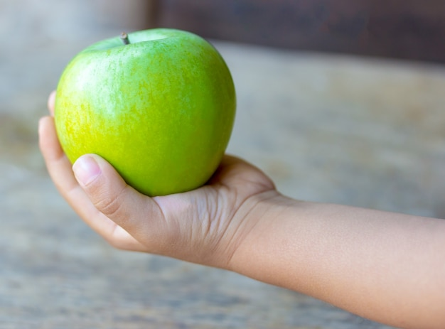 Kid holds a green apple