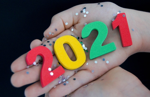 Kid holds in his hand multi colored numbers 2021 on a black background