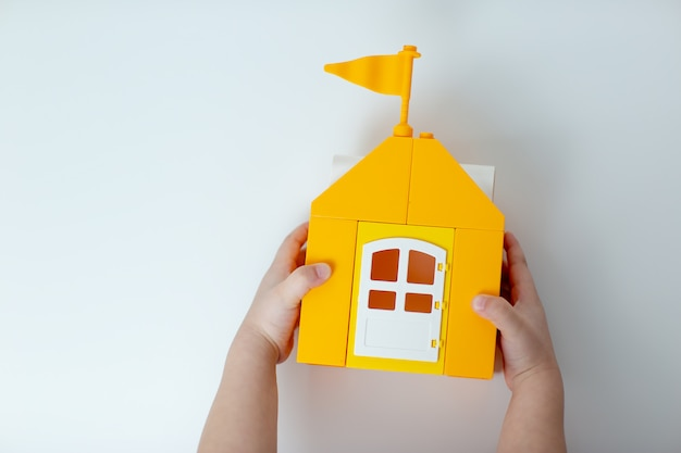 A kid holds lego house, stay home stay safe. yellow toy house with lego family. a kid self-isolation during virus.