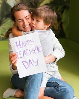 Ребенок обнимает счастливый учитель
