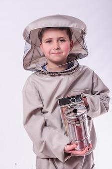 스튜디오 흰색 배경에서 포즈를 취하는 양봉가의 양복을 입은 아이.