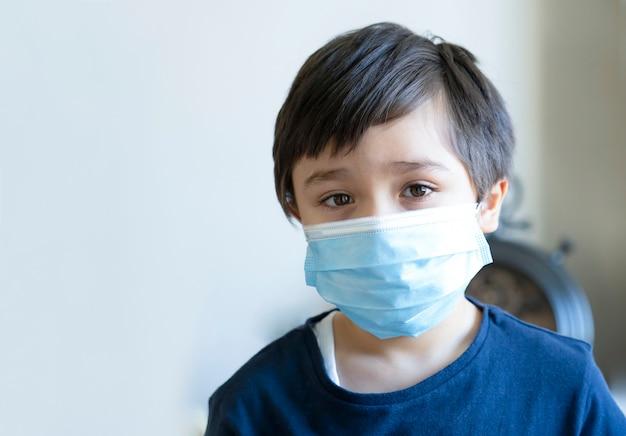 悲しそうな顔の医療用保護マスクを身に着けている子供、退屈した感じの子供男の子はコロナウイルスの家の検疫中に家にいなければなりません、covid-19の拡散に対する保護対策