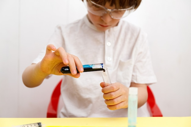 化学実験室で実験を行う安全メガネと白いtシャツを着た子供。化学のためのフラスコを持つ小さな男の子。ホームスクーリング。