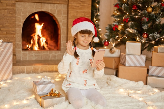 Ребенок в шляпе санта, имея веб-чат с кем-то, глядя на экран и махая рукой. милая девочка дошкольника с двумя косичками в шляпе санта-клауса и белом пуловере.