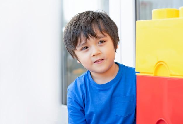 カラフルなプラスチックの箱を隠している自己分離の子供、遊びを楽しんでいる家庭の学生の子供は、遊び部屋でかくれんぼします。