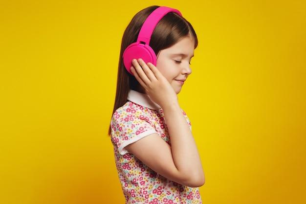 Ребенок в летней одежде слушает музыку в наушниках с закрытыми глазами