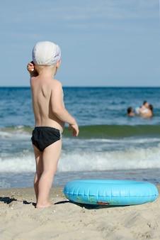 그의 뒤를 가진 해변에 수영 트렁크와 모자 서있는 아이가 거리를 찾습니다