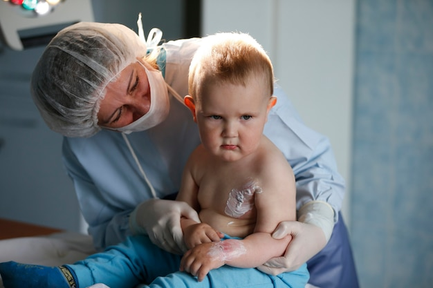 病院の子供が負傷しました医者は少し癒します男の子はやけどを負いました