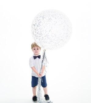 흰 셔츠를 입은 아이가 큰 풍선을 들고 있습니다. 큰 흰색 풍선입니다. 축 하 개념입니다. 파티 분위기. 광고 공간을 복사합니다. 비행 풍선을 들고 놀란된 소년입니다. 생일 파티 준비.