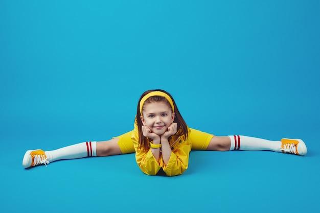 Ребенок в желтой одежде делает упражнения на растяжку шпагатом позы под прямым углом