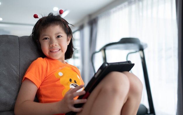 Kid is addicted to tablet, little girl playing smartphone, kid use telephone, watching cartoon