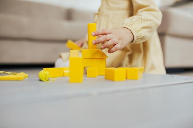 Малыш строит из желтых геометрических фигур