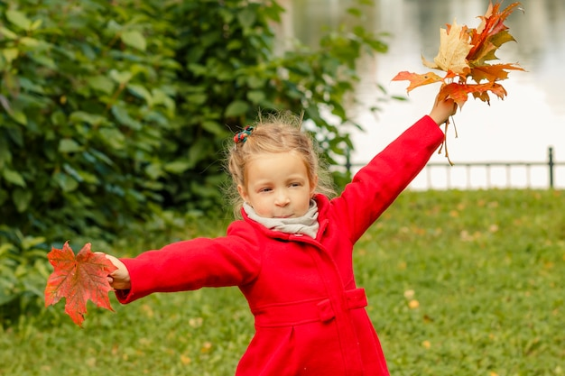 Kid is dancing with maple leaves.