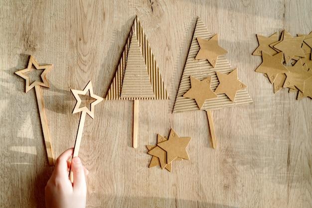 子供は彼の手でクリスマスツリーの装飾を持っています。子供はクリスマスツリーの飾りを見せています。ゼロウェイスト