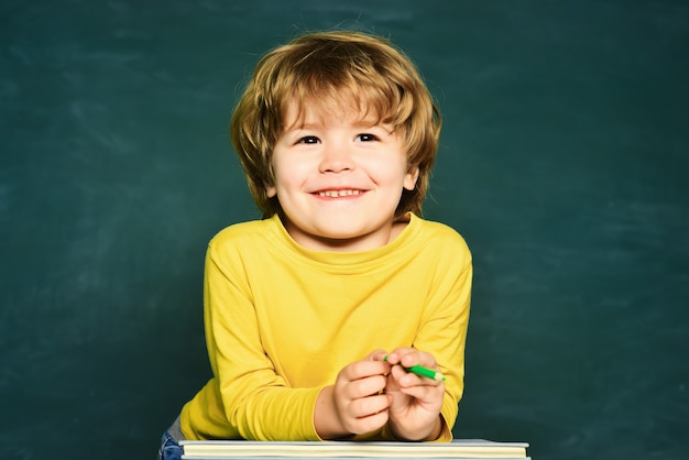 Kid is learning in class on background of blackboard educational process
