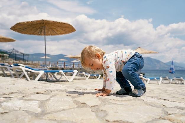 아이는 일광욕용 라운저와 우산이 있는 자갈 해변에 네 발로 서 있습니다