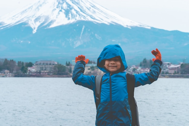 Kid is standing in front of kawaguchiko lake and mount fuji in winter.