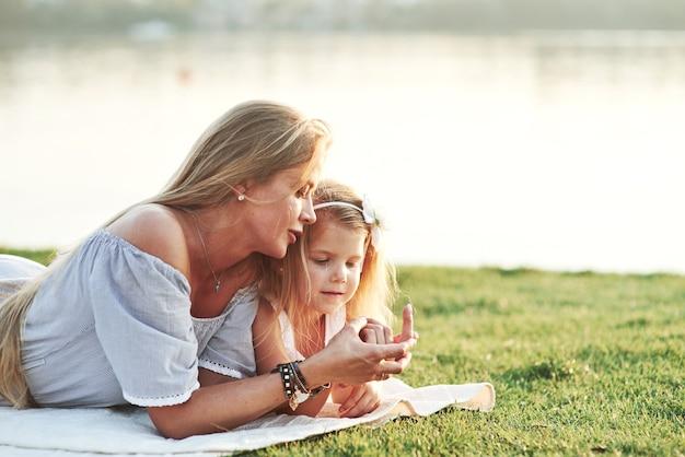 子供は、ママがどんなマニキュアを使っているのか疑問に思っています。湖を背景に緑の芝生で楽しい時間を過ごしている若い母と娘の写真。