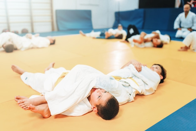 Kid judo, fight training, martial art, self-defense. little boys in uniform in sport gym, young fighters