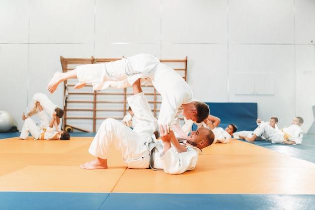 子供の柔道、訓練中の若い戦闘機。着物姿の小さな男の子がスポーツホールで武道を練習します。