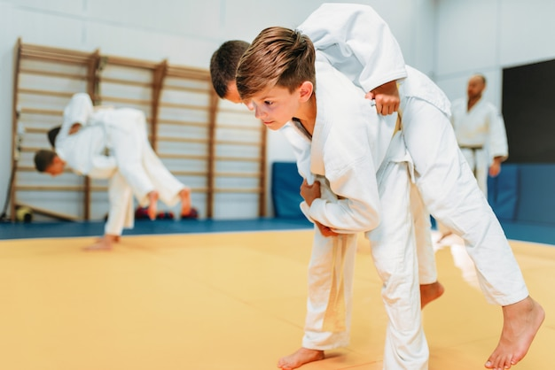 Kid judo, young fighters on training, self-defense. little boys in kimono practice martial art