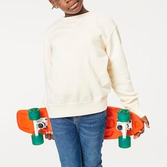 Kid in a jumper holding a skateboard