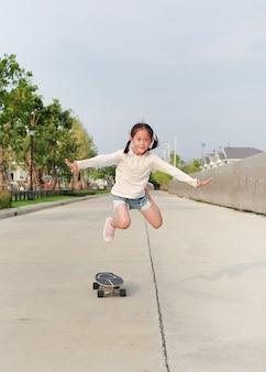 屋外でスケートボードに飛び乗る子供。スケートボードでスケートをするアジアの小さな女の子