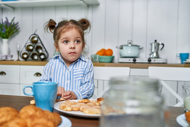 The kid in the kitchen wants to eat cookies with tea at home