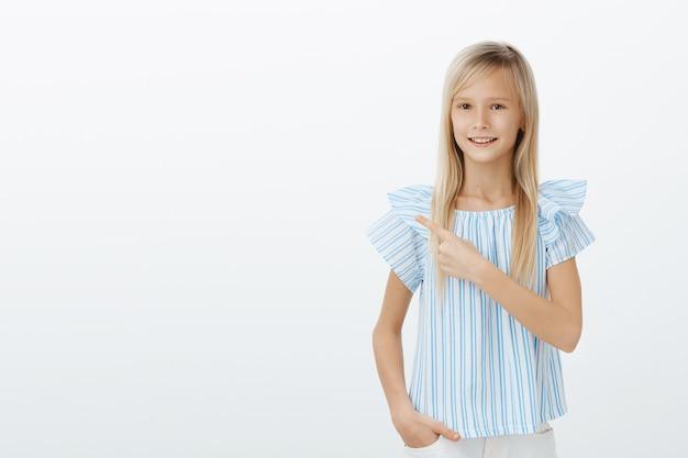 Малыш знает, что предлагает. кадр из помещения: уверенная в себе дружелюбная молодая девушка в модной синей блузке, указывающая в левый верхний угол и улыбающаяся, уверенная подруга у серой стены