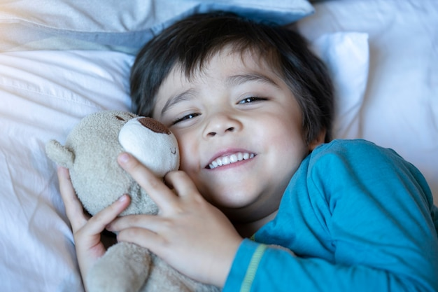 Kid laying in bed with teddy bear