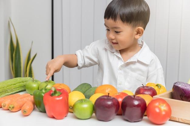 Ребенок учится о питании, как выбирать еду свежих фруктов и овощей.