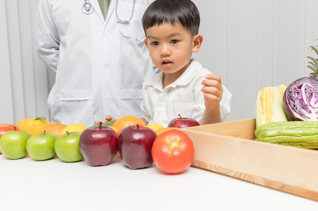 Kid learning about nutrition with doctor to choose how to eat fresh fruits and vegetables.
