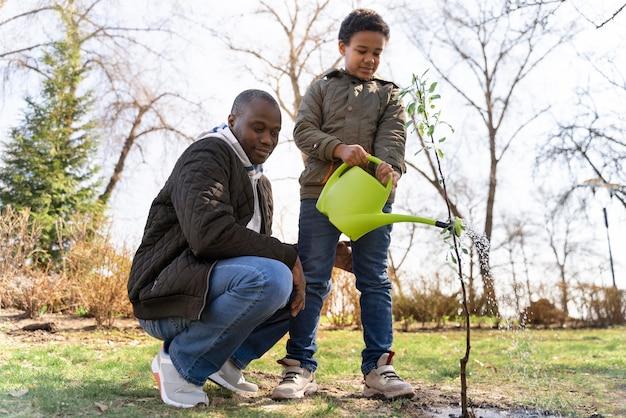Bambino che impara a piantare un albero