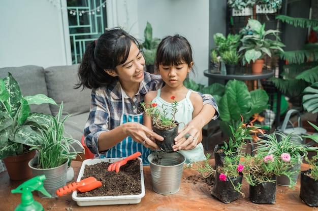 いくつかの植物を植えるガーデニングを行う方法を学ぶ子供